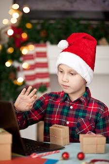 Junge in der weihnachtsmannmütze, die eine geschenkbox hält und ein digitales tablet-laptop-notizbuch verwendet.