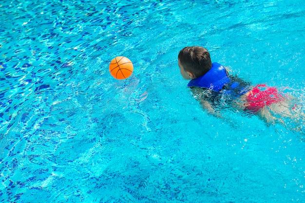Junge in der weste am swimmingpool mit ball, hintere ansicht. kindheit, freizeit, schwimmen