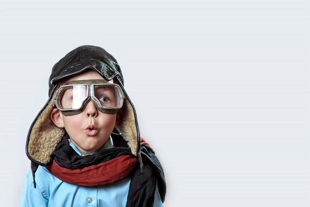 Junge in einem blauen hemd, einer pilotenbrille, einer mütze und einem schal