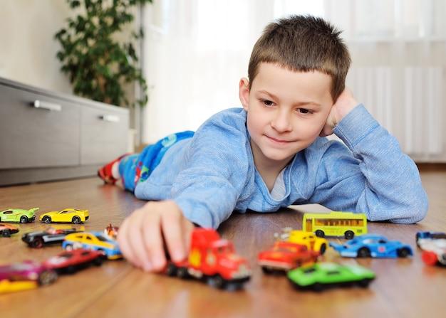 Junge in einem blauen pullover, der auf dem holzboden liegt