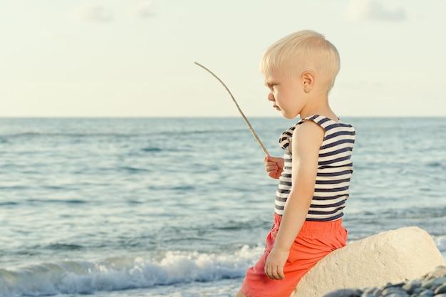 Junge in einem gestreiften t-shirt sitzt mit einem zauberstab am strand. meer im hintergrund