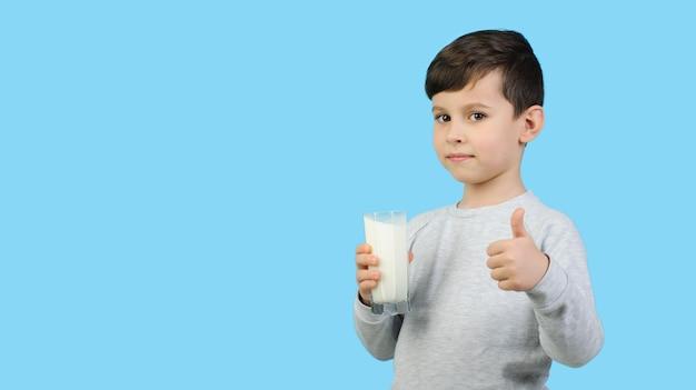 Junge in einem grauen pullover hält ein glas milch auf einem blauen isolierten hintergrund. der junge zeigt, dass er gerne milch trinkt. milchprodukte für kinder