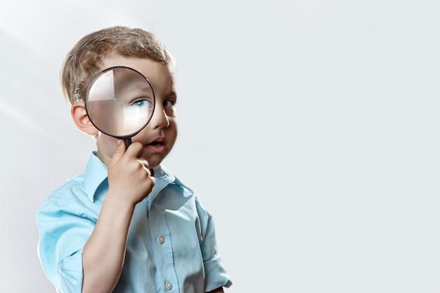 Junge in einem hellen t-shirt, das eine große lupe untersucht