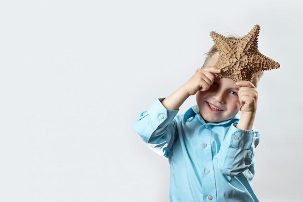 Junge in einem hellen t-shirt, das einen starfish auf einem weißen hintergrund hält