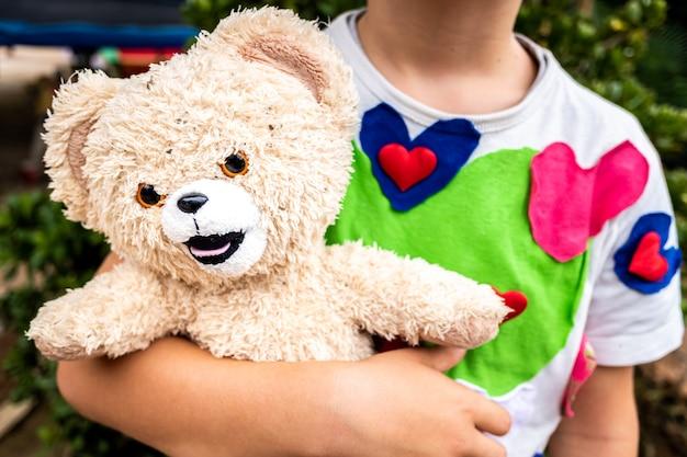 Junge in einem hemd verziert durch das halten seines alten und schmutzigen verlassenen teddybären.