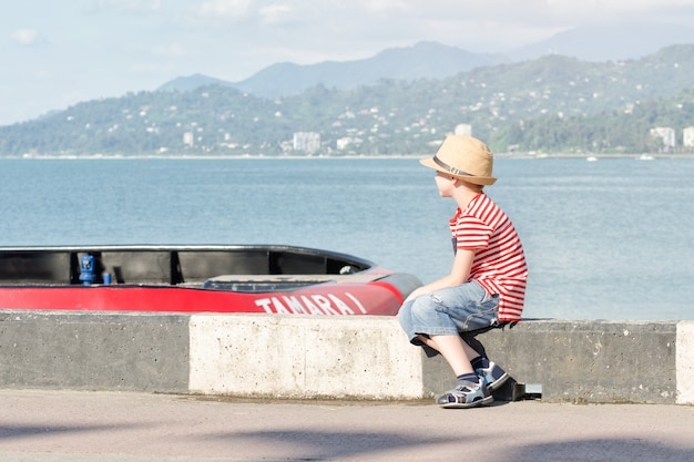 Junge in einem hut und in einem gestreiften t-shirt, die auf dem strand sitzen und betrachtet das schiff. seitenansicht