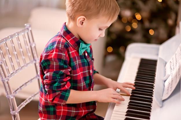 Junge in einem karierten hemd und in einem bindungsschmetterling, die klavier spielen. weihnachtskonzept.