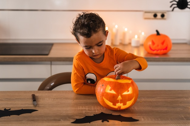 Junge in einem orangefarbenen kürbis-t-shirt mit blick auf seinen kürbis, der mit einer kerze angezündet wird, um seine halle zu dekorieren...