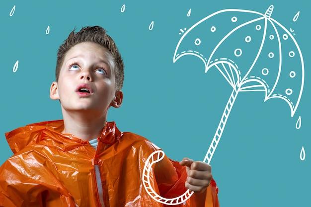 Junge in einem orangefarbenen regenmantel und mit einem bemalten regenschirm steht im regen