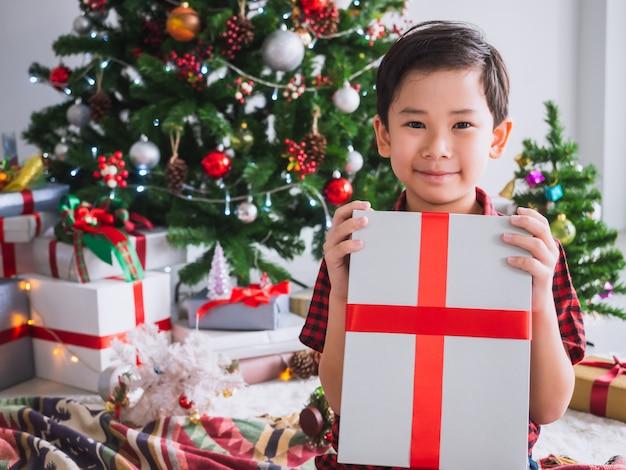 Junge in einem roten hemd hält geschenkbox und glücklich mit lustigem, weihnachten mit weihnachtsbaum zu feiern