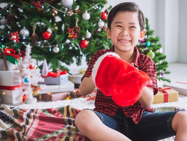 Junge in einem roten hemd hält rote socke und glücklich mit lustigem, weihnachten mit weihnachtsbaum zu feiern