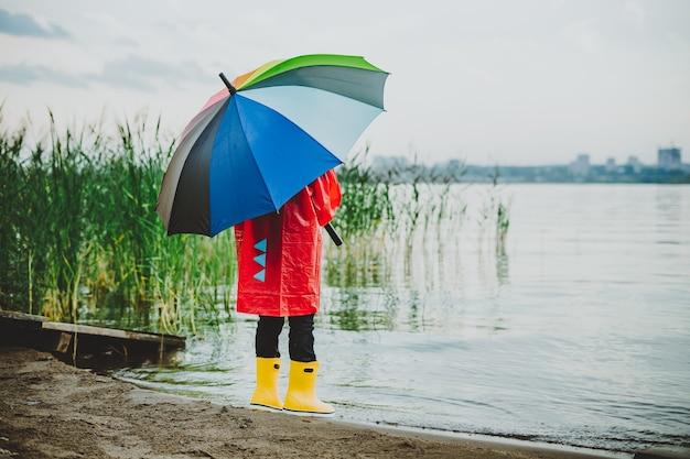 Junge in einem roten regenmantel und gelben gummistiefeln steht am flussufer und hält einen regenbogenregenschirm