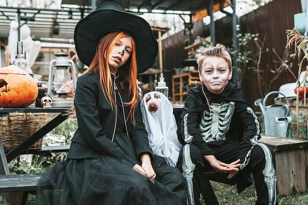 Junge in einem skelettkostüm und ein mädchen in einem hexenkostüm mit hund in einer geisterkostümhalloweenparty