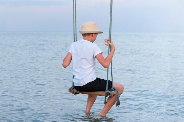 Junge in einem strohhut, der auf seil sitzt, schwingt über wasser