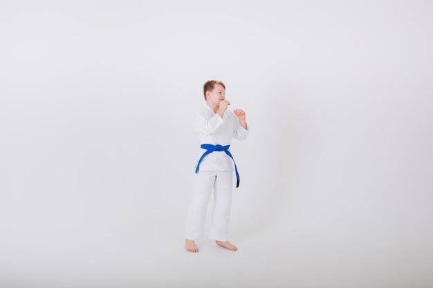 Junge in einem weißen kimono mit einem blauen gürtel steht seitlich in einer pose auf einer weißen wand