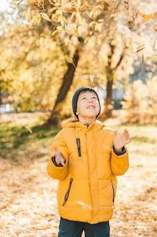 Junge in einer gelben jacke, verstreut blätter in einem herbstpark. das kind freut sich über das herbstlaub. glückliche kindheit. leuchtend gelbe jacke und blätter