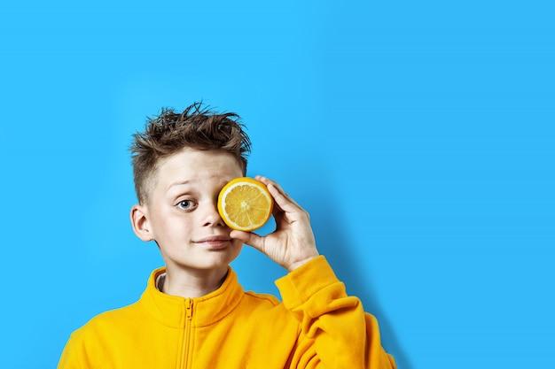 Junge in einer hellen gelben jacke mit einer zitrone in seiner hand auf einem blauen hintergrund