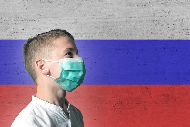 Junge in einer medizinischen maske auf seinem gesicht auf hintergrund der russischen flagge.