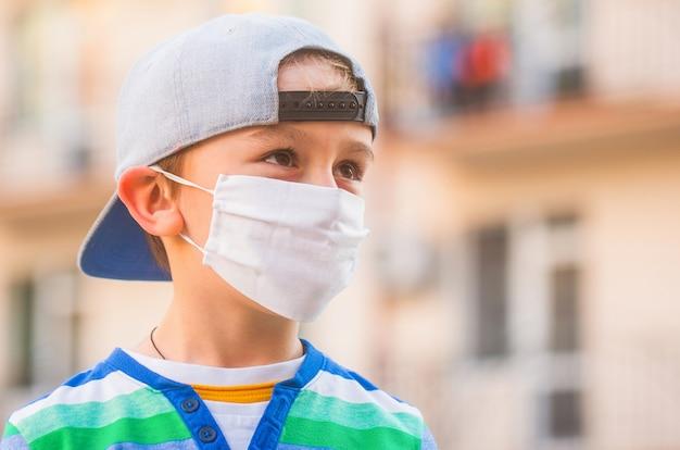 Junge in einer medizinischen maske. junge in einem chirurgischen verband.