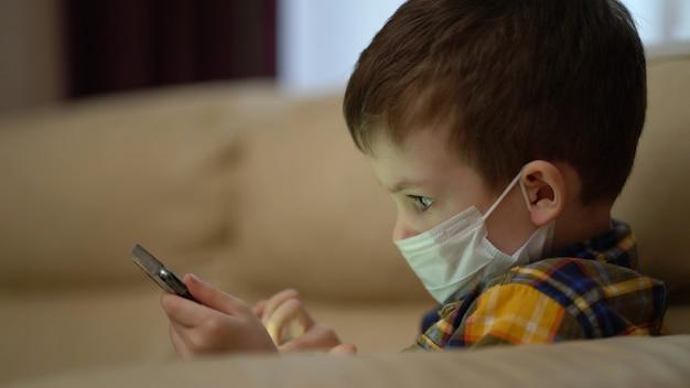 Junge in einer medizinischen maske schaut auf das telefon