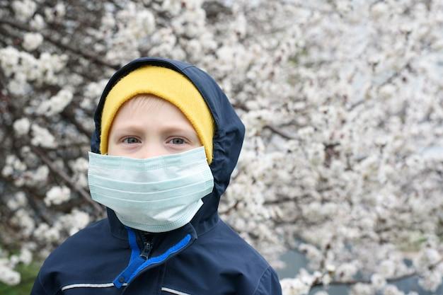 Junge in einer medizinischen schutzmaske draußen. blühender baum, frühlingstag