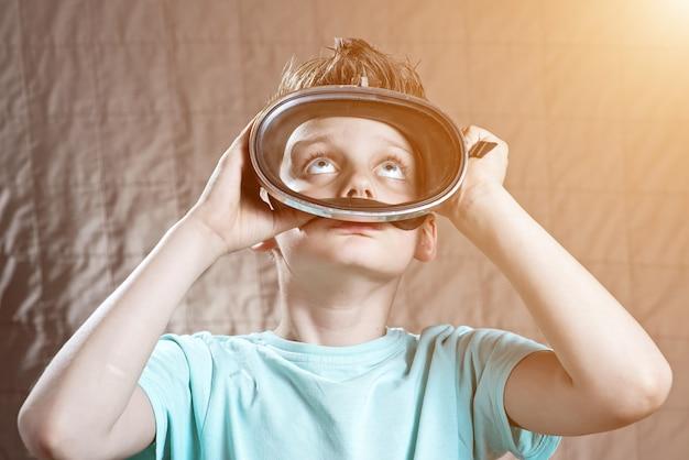 Junge in einer schwimmenmaske, die oben schaut