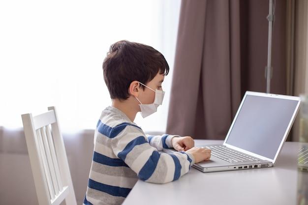 Junge in einer weißen medizinischen maske, sitzt hinter einem monitor mit einem laptop im zimmer
