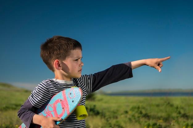 Junge in einer weste mit einem bunten skateboard