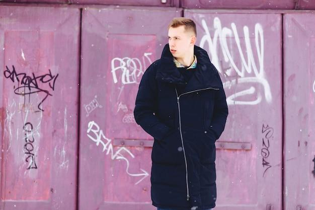 Junge in einer winterjacke vor dem hintergrund der wand