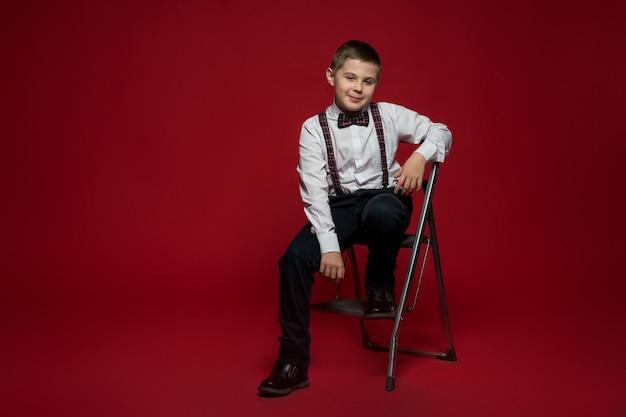 Junge in eleganten kleidern sitzt auf einer eisernen trittleiter gegen rote wand