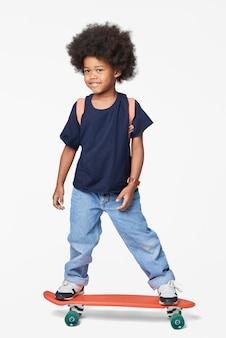 Junge in freizeitkleidung auf einem skateboard