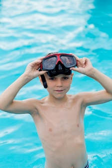 Junge in gläsern zum schwimmen steht im wasser