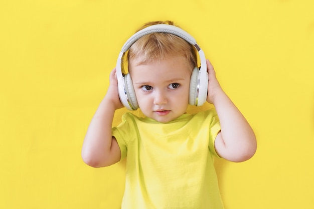 Junge in kopfhörern auf einem leuchtend gelben hintergrund hört aufmerksam und aufmerksam zu.