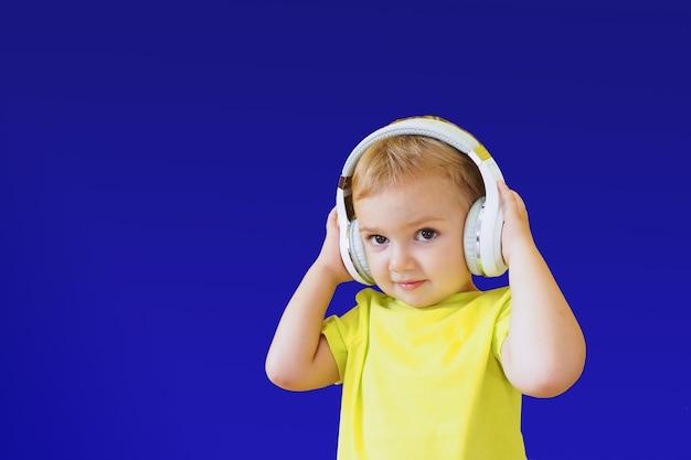 Junge in kopfhörern auf strahlend blauem lächeln und hört aufmerksam zu.