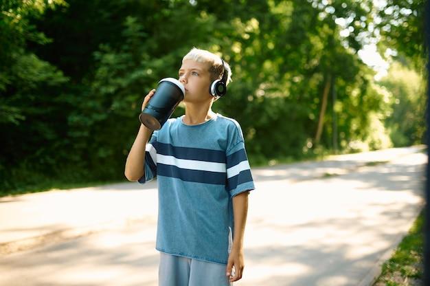 Junge in kopfhörern trinkt wasser auf dem wanderweg im freien. kind mit kopfhörern, das im sommerpark aufwacht, kind hat durst
