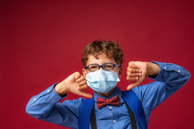 Junge in maske und brille, mit schulrucksack zeigt geste missbilligung