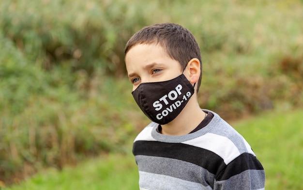 Junge in medizinischer schützender gesichtsmaske