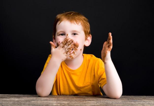 Junge in milchschokolade verschmiert, nachdem er schokolade geknabbert und gebissen hatte