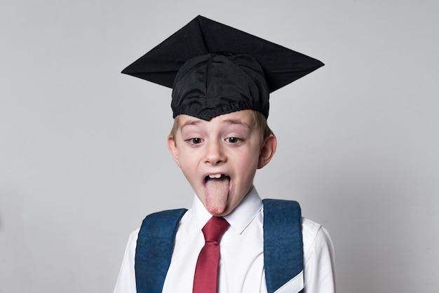 Junge in schuluniform und abschlusshut mit zunge. konzept der high school. schüler auf weißem hintergrund.