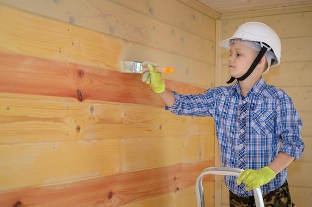 Junge in schutzfarbe malt die wand eines holzhauses, das auf einer leiter steht. ein holzhaus von innen mit öl für holz streichen