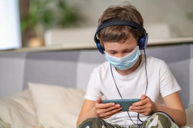 Junge in schutzmaske und kopfhörern, mit smartphone in den händen.