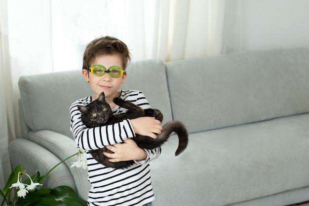 Junge in schwimmbrille hält eine schwarze katze und träumt davon, im sommer zu schwimmen