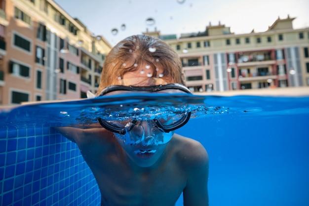 Junge in taucherbrille schwimmen im pool im hotel?