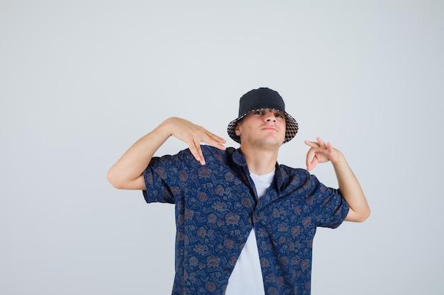 Junge in weißem t-shirt, blumenhemd, kappe, die ok zeichen zeigt und handgesten tut und zuversichtlich schaut, vorderansicht.