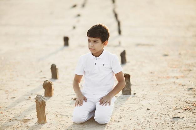 Junge in weißen kleidern sitzt auf seinen knien im sand auf dem sonnenuntergang