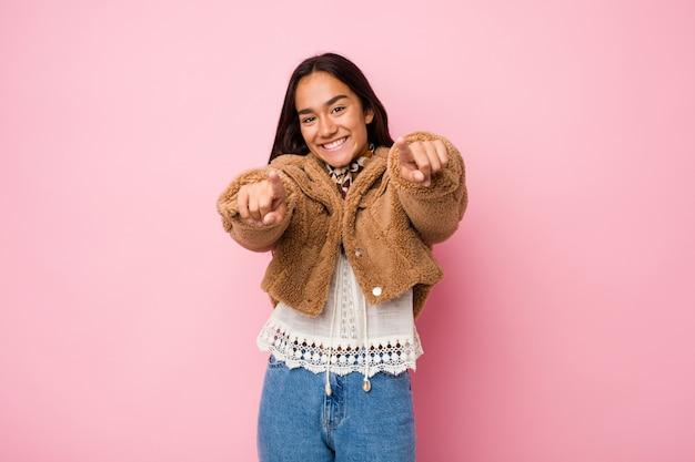 Junge inderin der gemischten rasse, die ein kurzes schafsfellmantel trägt, lächelt nach vorne.