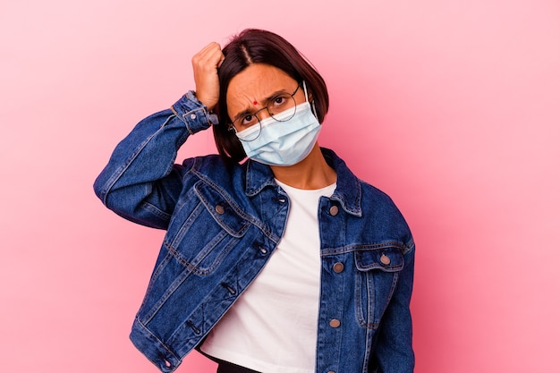 Junge inderin, die ein masken-antivirus trägt, das auf rosa isoliert ist, schockiert, sie hat sich an wichtiges treffen erinnert.