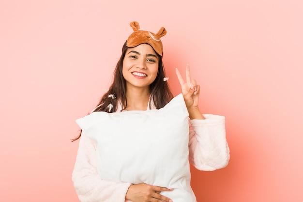 Junge inderin, die einen pyjama und eine schlafmaske trägt, isoliert, die ein kissen hält junge inderin, die einen pyjama und eine schlafmaske isoliert trägt, die das siegeszeichen zeigt und breit lächelt. <mixto>