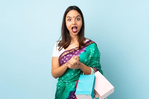 Junge inderin mit einkaufstüten mit überraschtem gesichtsausdruck