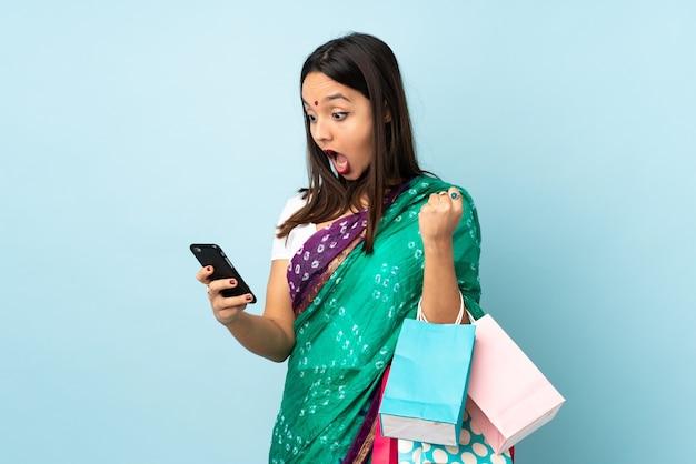 Junge inderin mit einkaufstüten überrascht und eine nachricht sendend